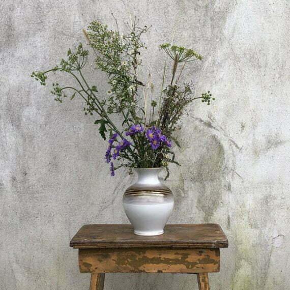 Porcelanowy wazon wypełniony polnymi trawami